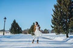 雪道的走的新娘 一个短的婚礼礼服,土气样式的美丽的浅黑肤色的男人,与杉木树婚礼花束,和 免版税图库摄影