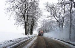 雪铺砂机洒在路的盐 库存照片
