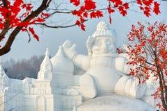 雪雕和红色叶子 免版税库存照片