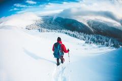 雪靴的一个人在山在冬天 免版税库存图片