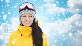 滑雪风镜的愉快的少妇在蓝天 免版税库存图片
