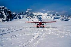 雪飞机着陆在阿拉斯加的山顶部的一个美丽的冬天妙境 库存照片
