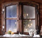 雪驯鹿和被点燃的蜡烛在窗玻璃 图库摄影