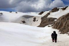 雪高原的两个远足者 库存图片