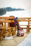 滑雪靴、手套和一个背包在一个室外酒吧在滑雪胜地 免版税库存照片