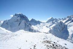 雪崩中断盖帽留下了山准备好的正确的树荫发光的倾斜雪山顶给顶层 免版税图库摄影