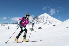滑雪登山冠军:女孩滑雪在滑雪的登山家攀登在背景火山 免版税库存图片
