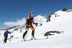 滑雪登山冠军:妇女滑雪在滑雪的登山家攀登在背景火山 免版税图库摄影