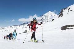 滑雪登山冠军:小组滑雪在滑雪的登山家攀登在背景火山 免版税库存照片