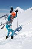 滑雪登山冠军:滑雪对山的登山家攀登与滑雪被束缚到背包 免版税库存图片