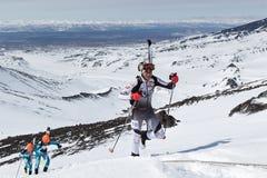 滑雪登山冠军:滑雪对山的登山家攀登与滑雪被束缚到背包 免版税库存照片