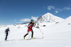 滑雪登山:女孩滑雪在滑雪的登山家攀登在背景火山 免版税库存照片