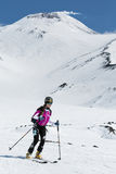 滑雪登山:妇女滑雪登山家乘坐从火山的滑雪 库存照片