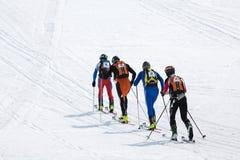 滑雪登山:小组滑雪对山的登山家攀登在滑雪 免版税库存图片