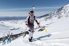 滑雪登山:滑雪对山的登山家攀登与滑雪被束缚到背包 免版税库存图片
