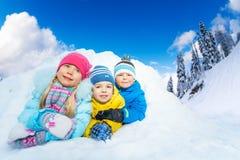 从雪洞的三个小孩微笑 库存照片