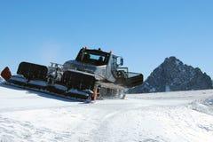 滑雪滑雪道雪在山的groomer机器 免版税库存图片