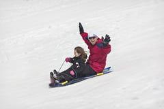 雪sledding乐趣 免版税库存图片