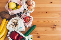 零的废购物概念 在eco棉花袋子的新鲜的杂货在木桌,平的位置上 从市场的菜在可再用的袋子 库存照片