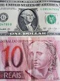 10雷亚尔巴西钞票和一美国美金、背景和纹理 免版税库存图片