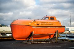 雷克雅未克,冰岛- 2017年10月14日:在海岸的海事安全和生存培训中心小船 橙色小船或救生艇 免版税库存照片