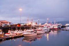 雷克雅未克,冰岛- 2017年10月14日:在海码头光的游艇在黄昏 在海岸的帆船在晚上天空 水运输a 免版税库存照片