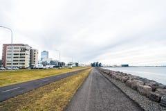 雷克雅未克,冰岛- 2017年10月12日:沿海的城市道路多云天空的 散步在海边 自由、透视和未来 免版税图库摄影