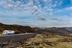 雷克雅未克,冰岛- 2014年10月15日:与山和卡车的冰岛风景在路 青苔和熔岩地面 库存照片