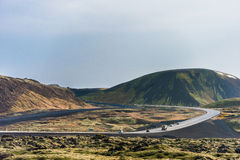 雷克雅未克,冰岛- 2014年10月15日:冰岛与路、山和青苔的风景自然在熔岩地面 库存图片