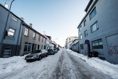 雷克雅未克,冰岛- 3月1日-冬天街道,有汽车的结冰的路在斜向一边雷克雅未克, 2017年3月01日的冰岛停放了 免版税库存图片