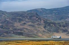 雷克雅未克-冰岛- 2016年10月15日:与山、蓝天和卡车的冰岛风景在路 库存照片