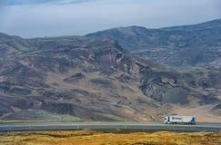 雷克雅未克-冰岛- 2016年10月15日:与山、路和卡车的冰岛风景 库存照片