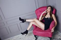黑贝雷帽和一件短的丝绸礼服的美丽的年轻性感的深色的妇女抽坐在桃红色扶手椅子时髦的凝块的香烟 免版税库存图片