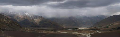 雷暴在Zanskar高地河谷:重的灰色云彩在峰顶落,幽暗包围小山,全景pho 库存图片