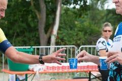 雷根斯堡,巴伐利亚,德国, 2017年8月06日,第28雷根斯堡三项全能2017年,赛跑者采取塑料杯子用水 免版税图库摄影
