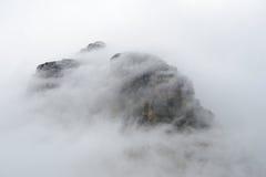 雾在冰川国家公园围拢一个山峰 库存图片