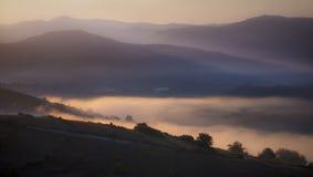 雾在日出的低谷山 库存照片