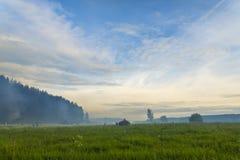 雾的人们在梦想的绿色草甸 免版税库存照片