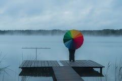 雾的女孩在有彩虹伞的码头 库存图片