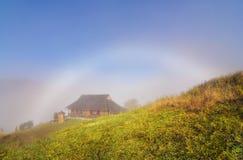 雾的山村与白色彩虹 免版税库存照片