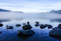 雾的蒂蒂湖与在前景的石头 免版税库存图片