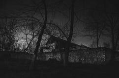 雾的议院在晚上在庭院里,鬼魂房子风景在黑暗的森林里 库存照片