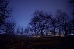 雾的议院在晚上在庭院里,鬼魂房子风景在黑暗的森林里 免版税库存图片