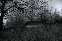 雾的议院在晚上在庭院里,鬼魂房子风景在黑暗的森林里 库存图片