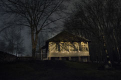 雾的议院在晚上在庭院里,鬼魂房子风景在黑暗的森林里 免版税图库摄影