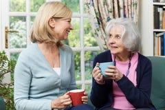 需要时间的妇女拜访资深女性邻居和谈话 库存图片