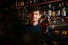 震动在振动器的年轻卷曲男服务员一个新鲜的夏天鸡尾酒 免版税库存图片
