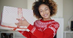 震动她的圣诞节装箱的礼物的美丽的女孩 股票录像