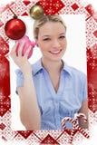 震动她的存钱罐的微笑的妇女的综合图象 免版税库存照片