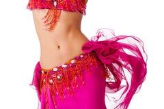 震动她的臀部的一套流行粉红服装的肚皮舞表演者 免版税库存图片